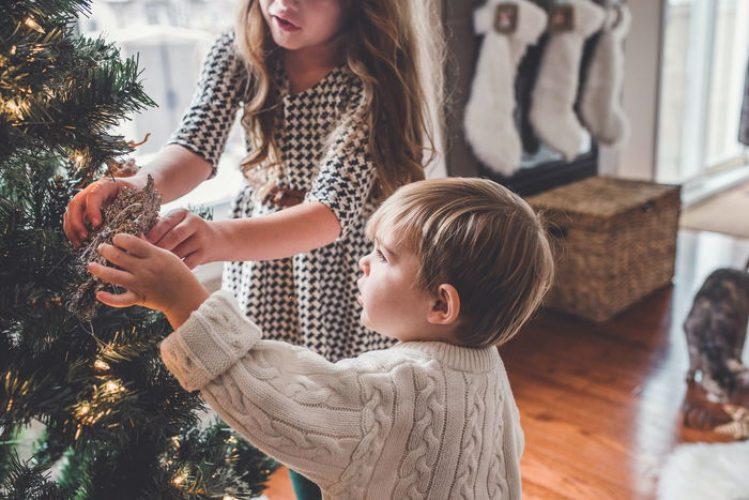 Enfant décorant un sapin artificiel